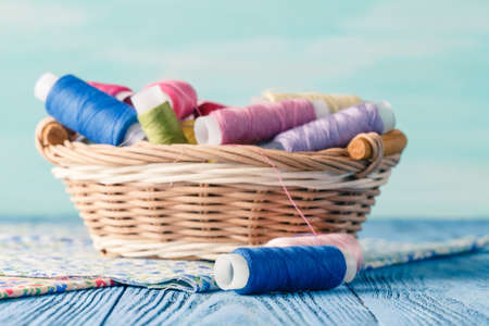 basket embroidery: threads in basket and soft toy on blue table