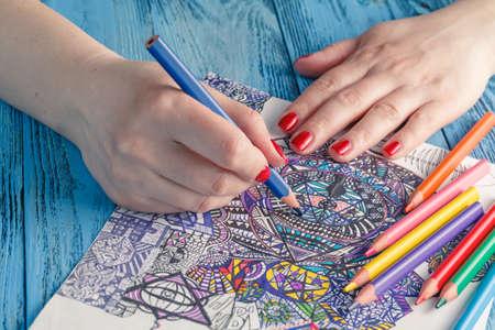 Libros para colorear para adultos en la mesa azul Foto de archivo - 56446706
