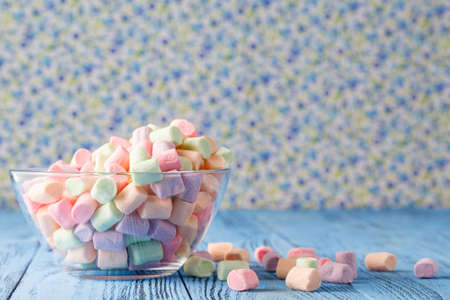 soft colors: Glass bowl of colored marshmallows on blue background Stock Photo