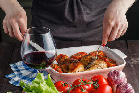 cook griddle: woman puts roast chicken on the table Stock Photo