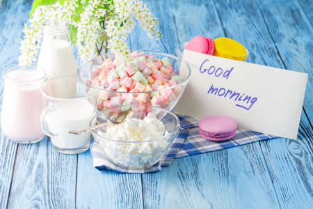 frence: Glass of milk with Tasty macaroon on with background and message good morning