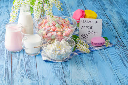 frence: Glass of milk with Tasty macaroon on wooden background and message have a nice day Stock Photo