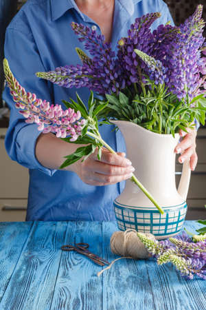 arranging: woman arranging a bunch of flowers in a vase