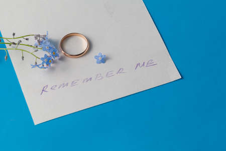 obituary: blue flowers (forget-me-not) on paper with message
