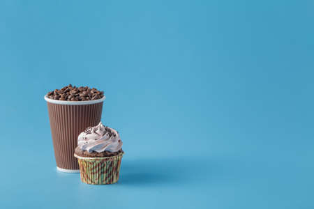 to go cup: Coffee to go Cup with coffee beans and cupcake on blue Stock Photo