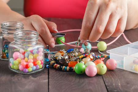 colorful beads: Woman making necklace from colorful beads