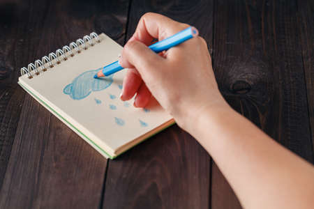adult hand: Woman drawing blue rain in notebook. Stock Photo
