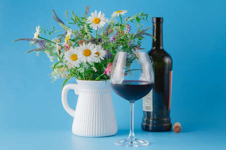 Glass of Red Wine with Wildflowers on blue background