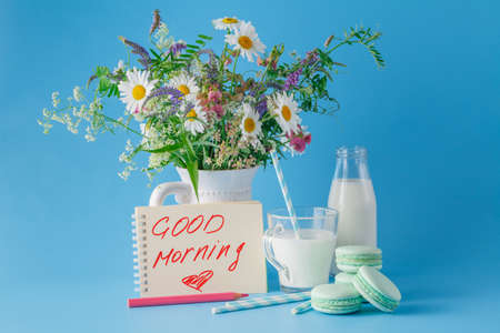 phrase: Breakfast with wildflowera, sweets and hand writing phrase good morning Stock Photo