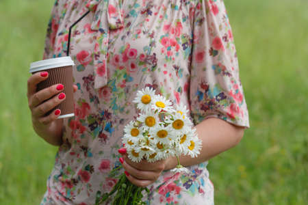 summer vacation, leisure, drinks and people concept - close up of woman with coffee cup with flowers in park