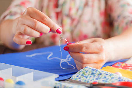 elusive: Thread insert into a needle in woman hands on table Stock Photo