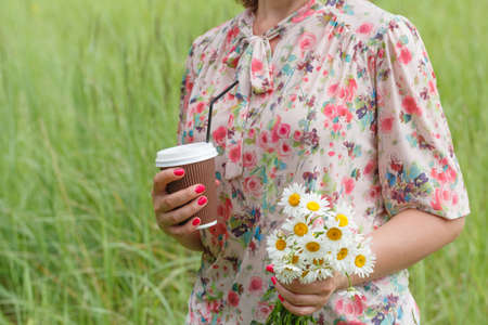 Female hand with paper cup of coffee outdoors with wild flowers, closeup