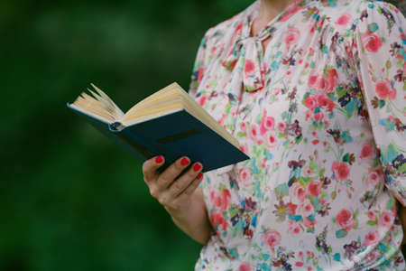 illiterate: Adult woman reading an open book old book. Knowledge, Science. Stock Photo