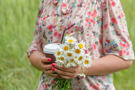 Summer concept, anonymous woman hold takeaway coffee cup on sunny day