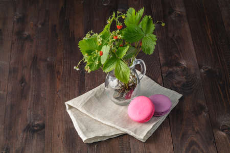 berryes: Colorful French Dessert Macaroons, Flowers, Berries on Rustic Wooden Background. Stock Photo