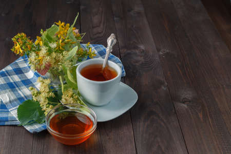 linden tea: Herbal medecine: Cup with linden tea and flowers on wooden table