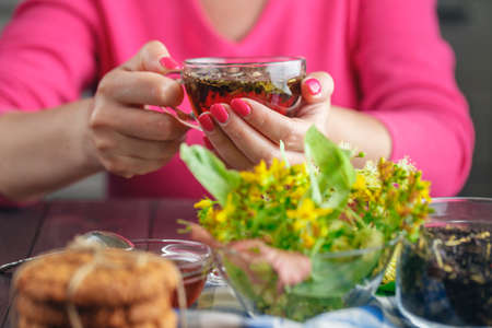 limetree: Woman with red nail polish holding tea cup with herbs