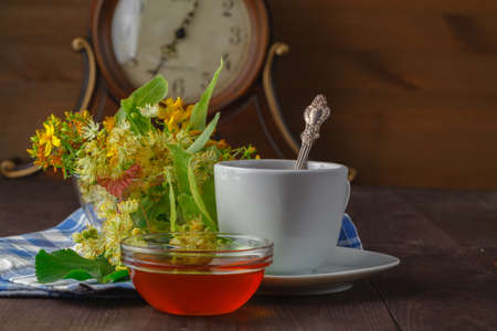 medecine: Herbal medecine: Cup with linden tea and flowers on wooden table