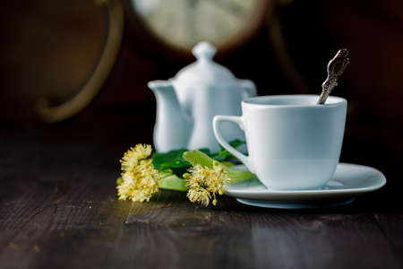linden blossom: tea cup and Linden blossom on evening wooden table