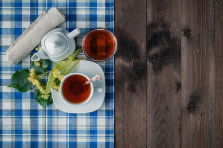 linden blossom: Herbal tea with flowers on blue napkin Stock Photo