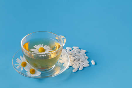 dietary supplements: Cup of chamomile tea in transparent mug, served with dietary supplements pill Stock Photo