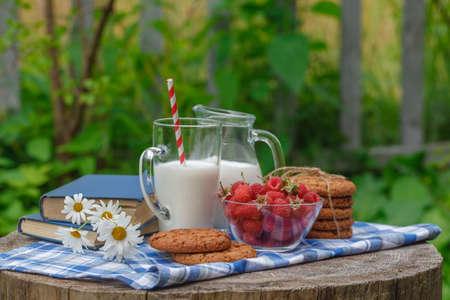 breakfast garden: glass of milk and bowl of fresh berries in an outdoor setting, healthy breakfast in the garden