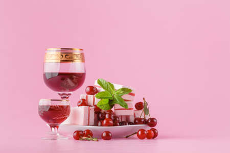 Cherry liqueur and sweets on plain pink backhround