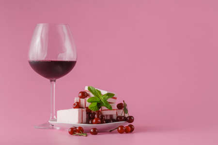cordial: Cherry wine in glass on pink background with sweets