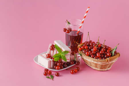 glass of cherry juice with fresh cherries berry on pink background. Vitamins and minerals. Healthy drink concept.