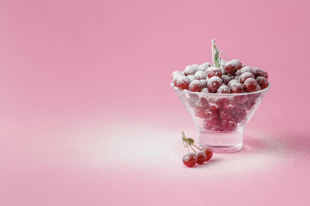 sugar powder: raw fresh cherries in glass with sugar powder