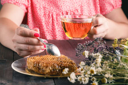 chamomilla: Cup of herbal tea with wild flowers and various herbs