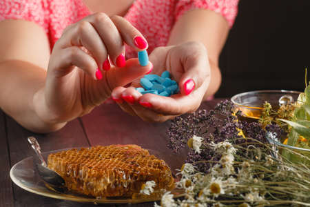 Healthcare and medicine: Young woman has control over pills with relax  herbs Stock Photo