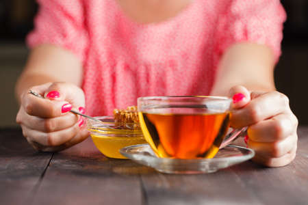 Woman drink tea and honey on wooden table. Stock Photo