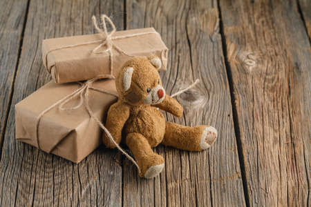 bear s: Valentines day homemade gifts in craft paper with hearts tags, Toy bear on wooden rustic table