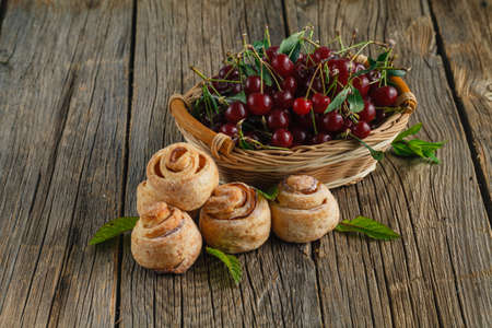 strudel: cherries and cherry turnover with a tea cup on wooden  background