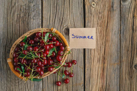woden: cherries in the basket on woden table with tag summer