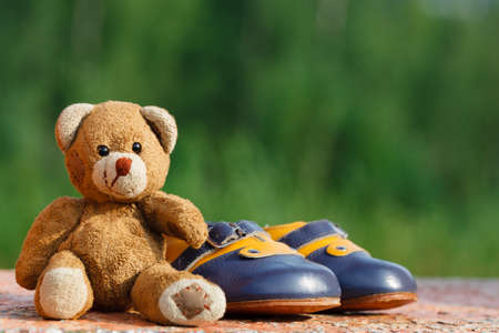 Vintage baby shoes with teddy bear