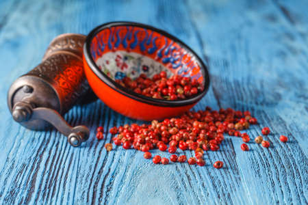 Bowl of pink pepper on blue table
