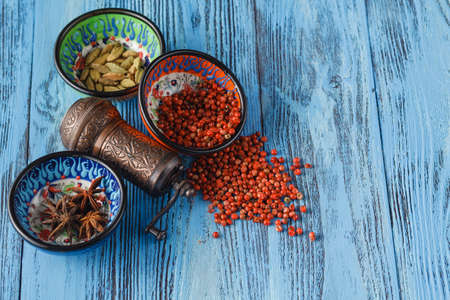 Few spices scattered on a table and mill Stock Photo