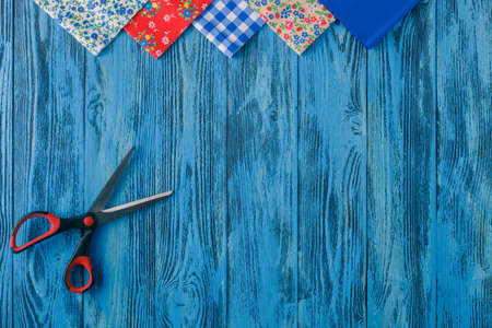 Sewing background. Accessories for needlework on wooden background. Spools of thread, scissors, buttons, measuring tape, sewing supplies. Set for needlework top view