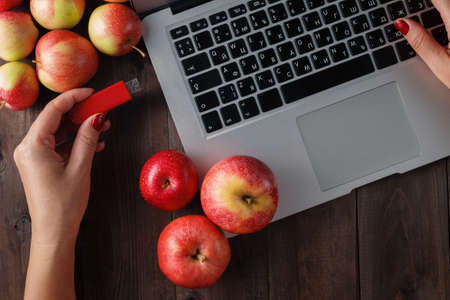pendrive: Close up of woman hand plugging red pendrive on  laptop with apple