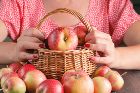 give out: woman  holding a basket of apples Stock Photo