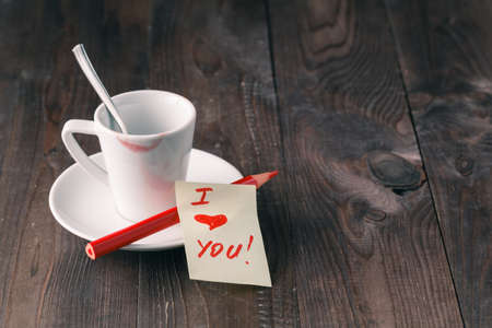 wenge: Cup of coffee with lipstick mark and note i love you on table close up
