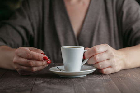 cappaccino: woman hands with espresso on a wood table