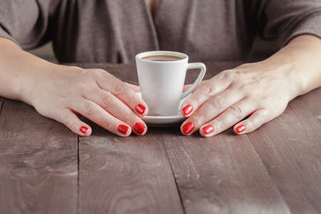 two object: Coffee break. Close up portrait of female hands holding cups of hot beverage espresso on rustic wooden table on dark background in fancy coffee shop, cafe. relaxation moment
