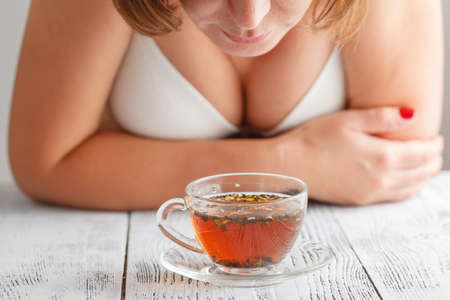 home comforts: Attractive woman with a cup of tea on the bed
