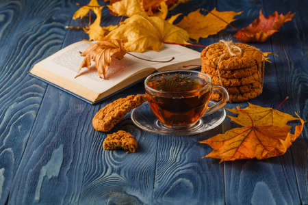 Cup of tea wit old book and autumn leaves on wooden table 写真素材