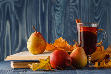 fall winter: Autumn still life : mulled wine with cinnamon, pear, autumn leaves, books and apple on a wooden background Stock Photo