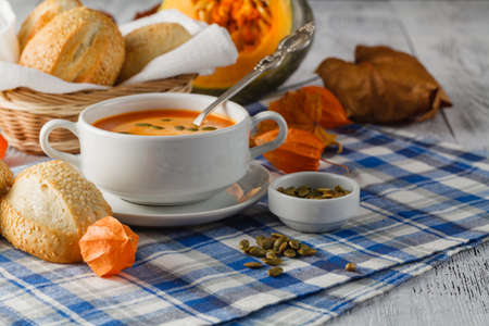 soup bowl: A bowl of spicy pumpkin soup, swirled with milk cream