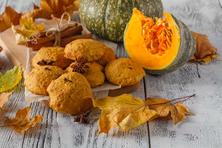Cookies pumpkin and cinnamon on the plate, brown cup on wooden boards background Stock Photo